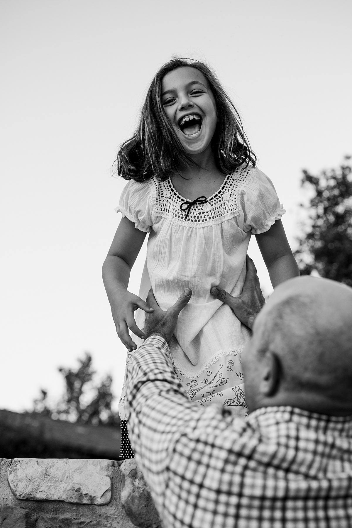 Orange County family photographer. Candid photo of dad reaching for his daughter as she jumps off stone wall during family photo shoot at Quail Hill with Krystil McDowall Photography