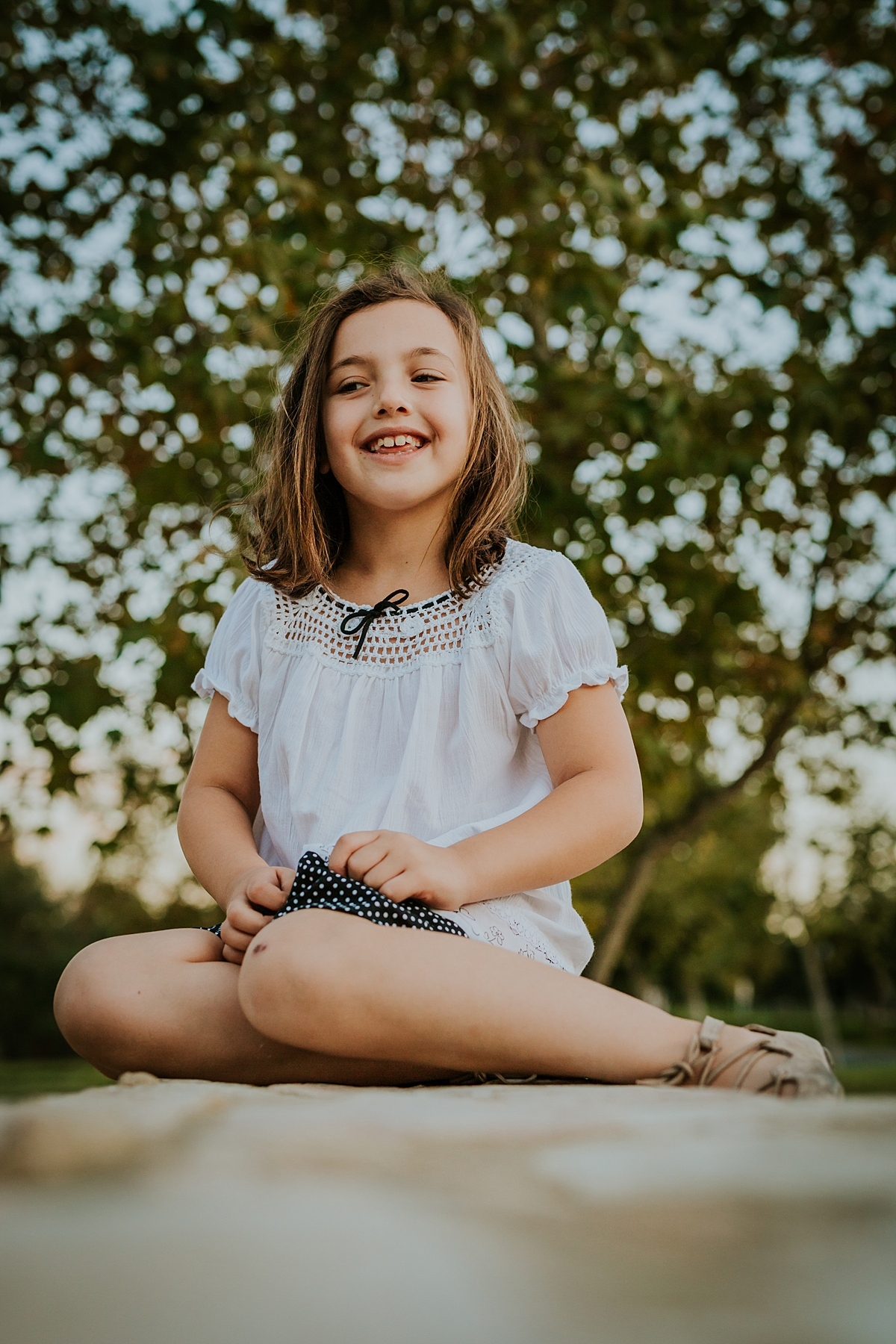 Orange County family photographer. Portrait of daughter as she sits on stone wall during family photo shoot at Quail Hill with Krystil McDowall Photography
