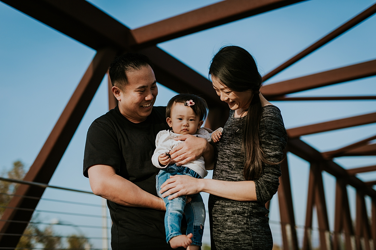 Orange County family photographer. Photo of mom, dad and sweet one year old daughter standing on bridge during outdoor family photo session at Jeffrey Open Space Trail in Irvine