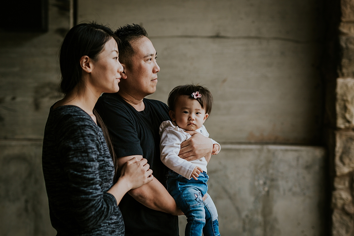 Orange County family photographer. portrait of mom, dad and their one year old daughter looking out from the bridge opening during outdoor family photo session at Jeffrey Open Space Trail Irvine