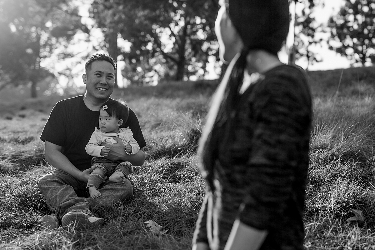 Orange County family photographer. photo of mom in foreground looking at dad and daughter while sitting in the grass during outdoor family photo session at Jeffrey Open Space Trail Irvine