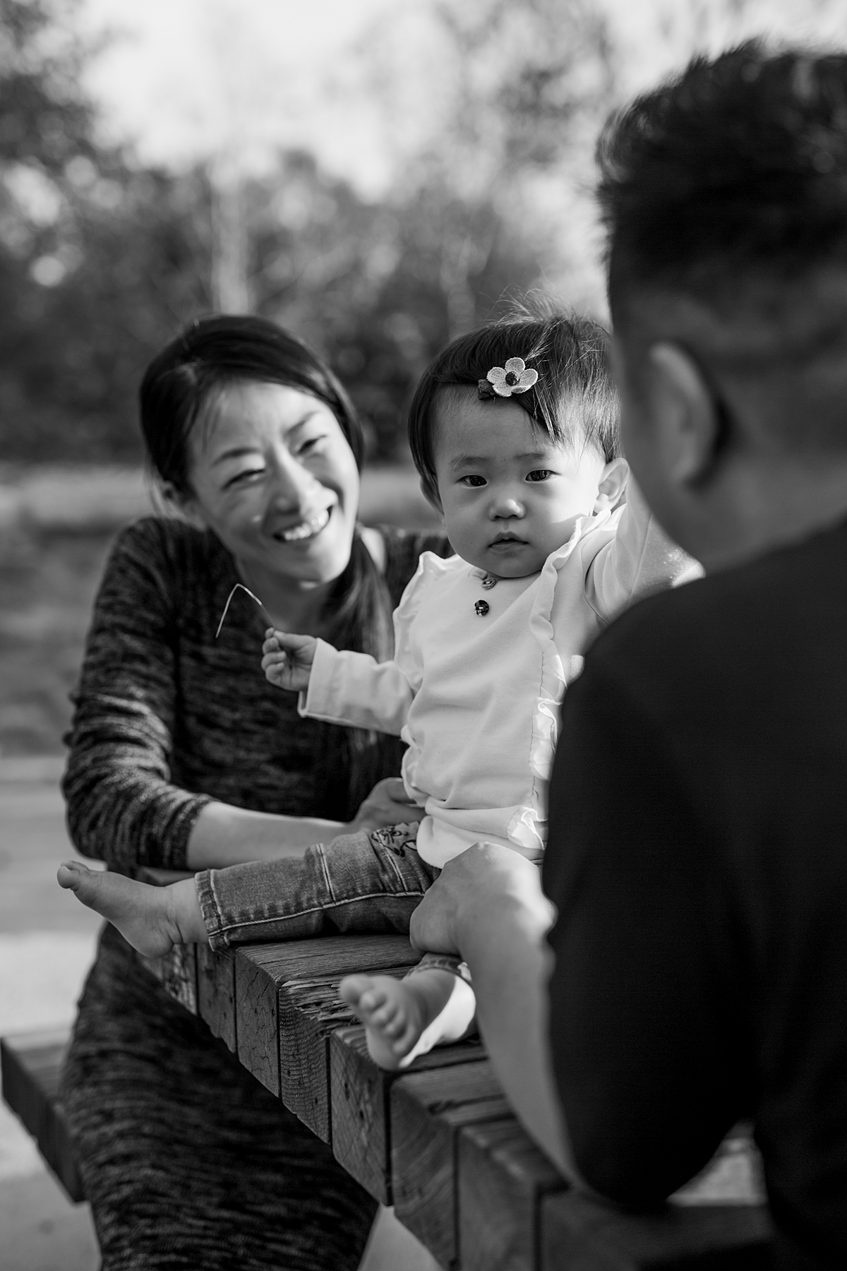 Orange County family photographer. Black and white photo of mom, dad and daughter sitting at park bench during outdoor family photo session at Jeffrey Open Space Trail Irvine