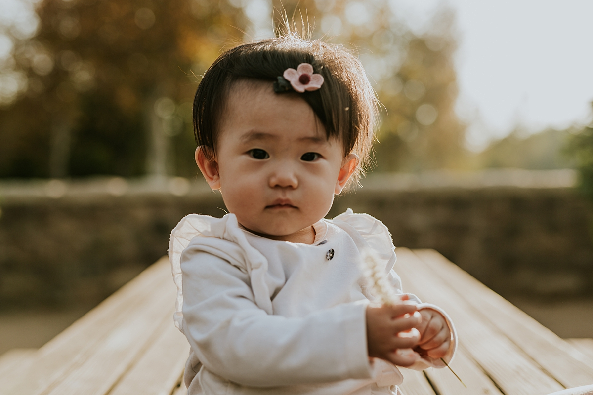 Orange County family photographer. Portrait of one year old girl with pink bow sitting on park bench during outdoor family photo session at Jeffrey Open Space Trail Irvine