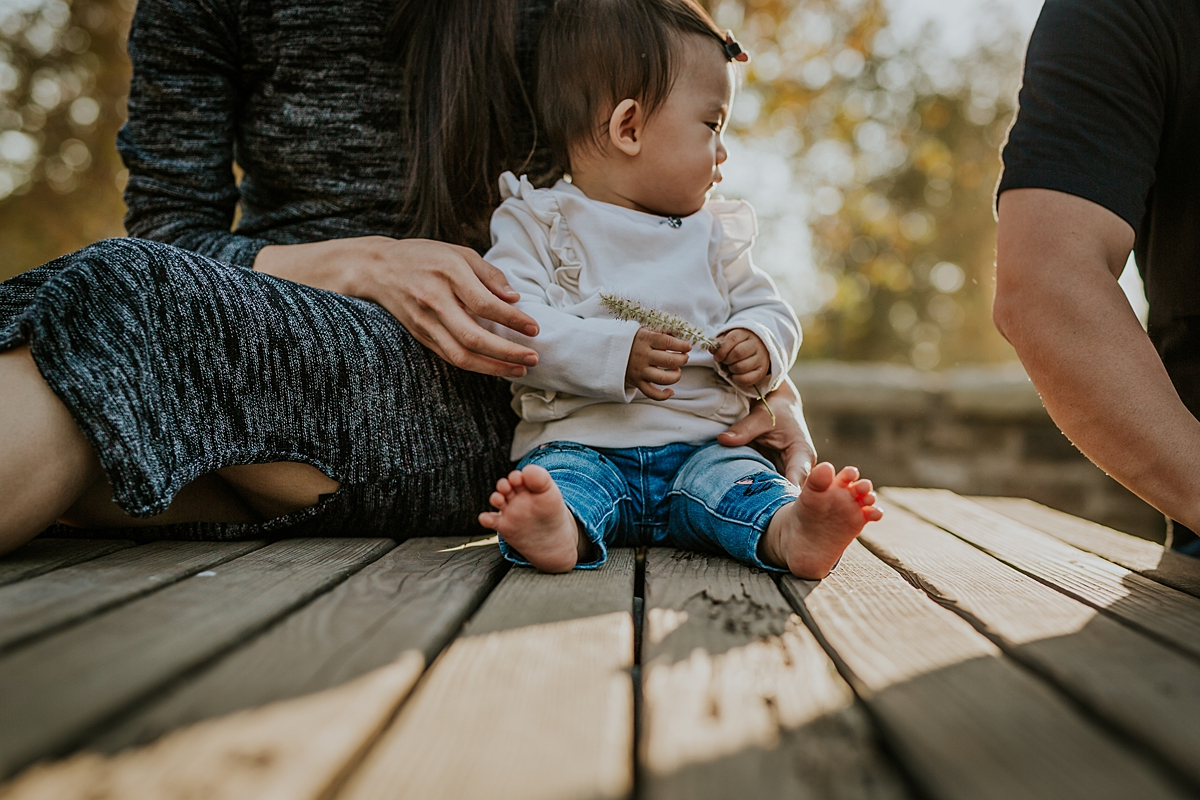 Orange County family photographer. Photo of girl sitting against her mama on a park bench during outdoor family photo session at Jeffrey Open Space Trail Irvine