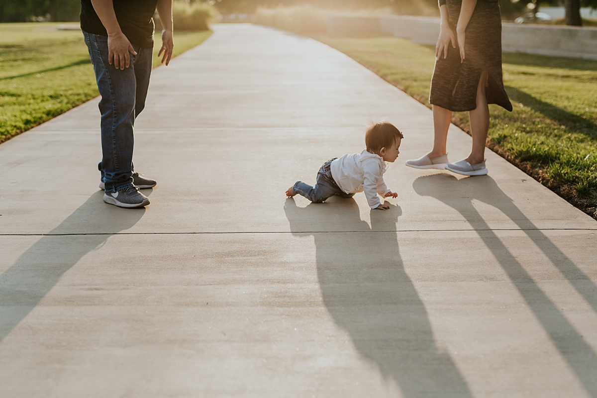 Orange County family photographer. Candid image of one year old girl crawling across the path with her mom and dad on either side at Jeffrey Open Space Trail Irvine