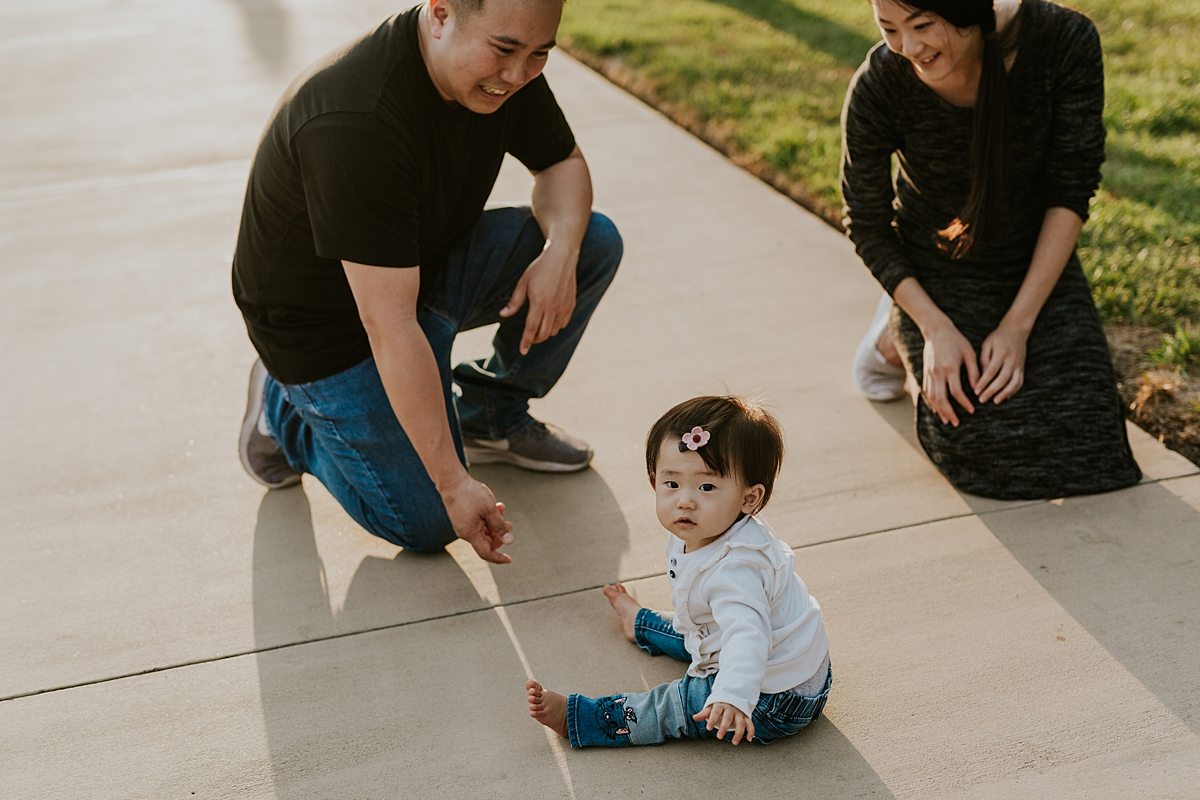 Orange County family photographer. Candid photo of family playing on path with sunset in the background during family photo shoot at Jeffrey Open Space Trail Irvine