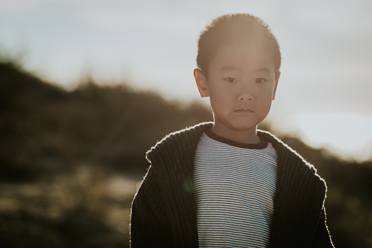 Orange County family photographer. Backlit portrait of boy in grey cardigan at Top of the World Laguna Beach during outdoor family photo session