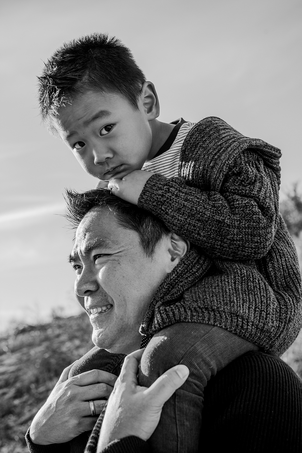 Orange County family photographer. B&W photo of dad giving his son a shoulder ride while son rests on dad's head at Top of the World Laguna Beach during outdoor family photo session