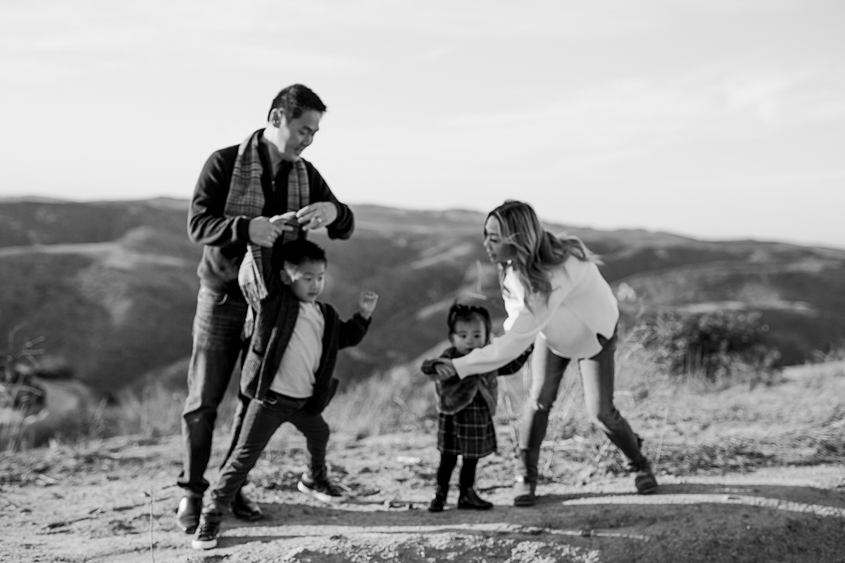 Orange County family photographer. Photo of family of four playing on dirt hill during during outdoor during family photo session at Top of the World Laguna Beach
