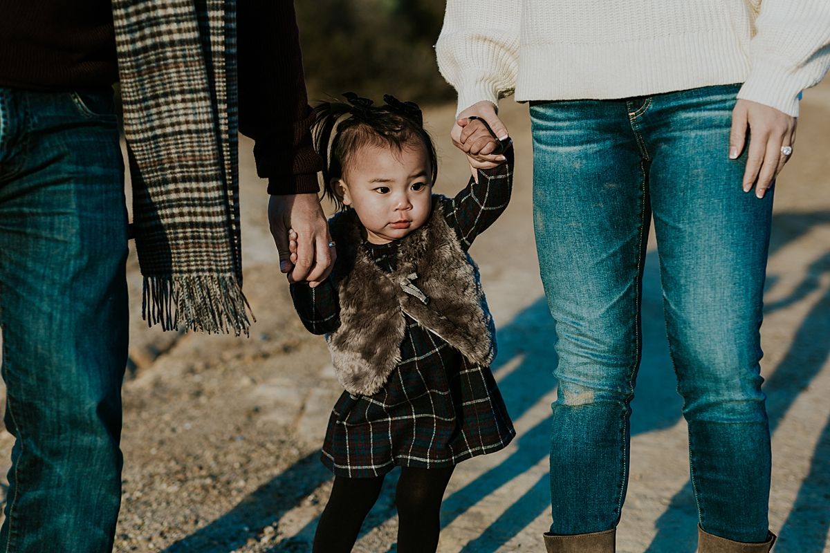 Orange County family photographer. Photo of toddler holding her mom and dad's hands before she gets swung in the air during outdoor during family photo shoot at Top of the World Laguna Beach CA
