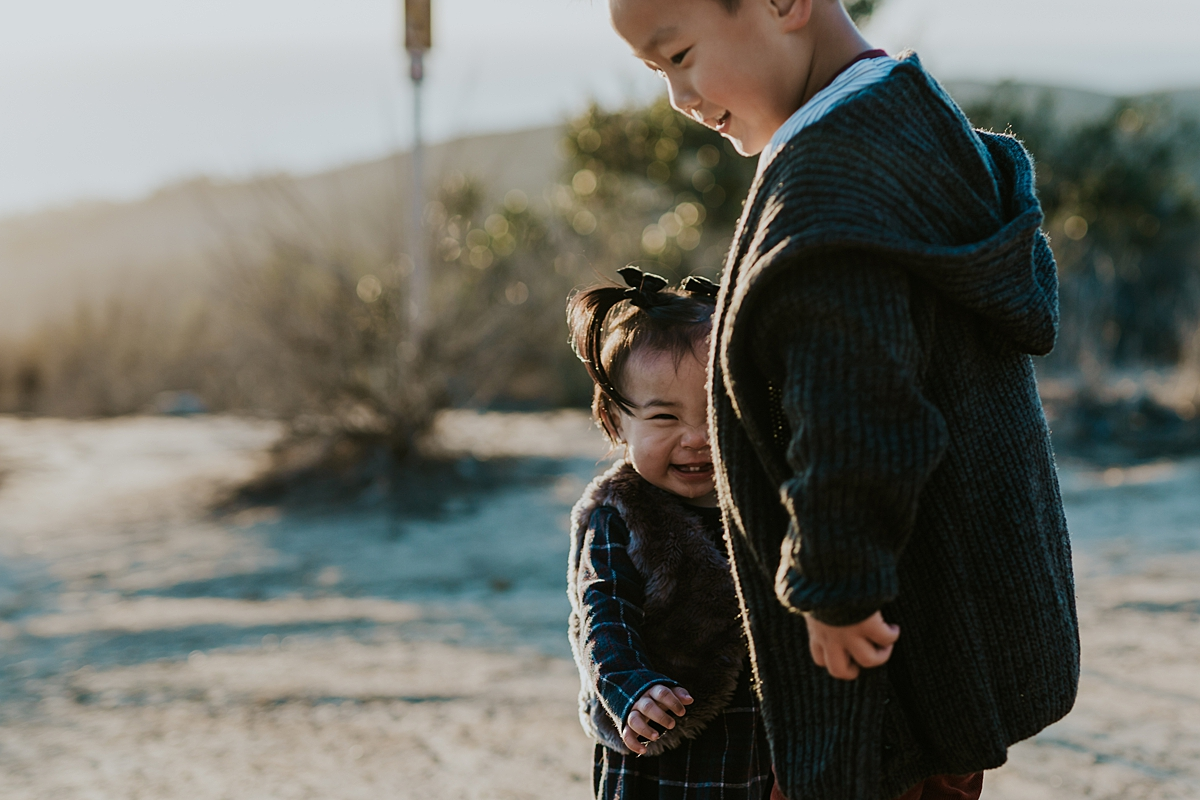 Orange County family photographer. Photo of brother and sister hugging while playing on a dirt road in the sun during outdoor during family photo shoot at Top of the World Laguna Beach CA