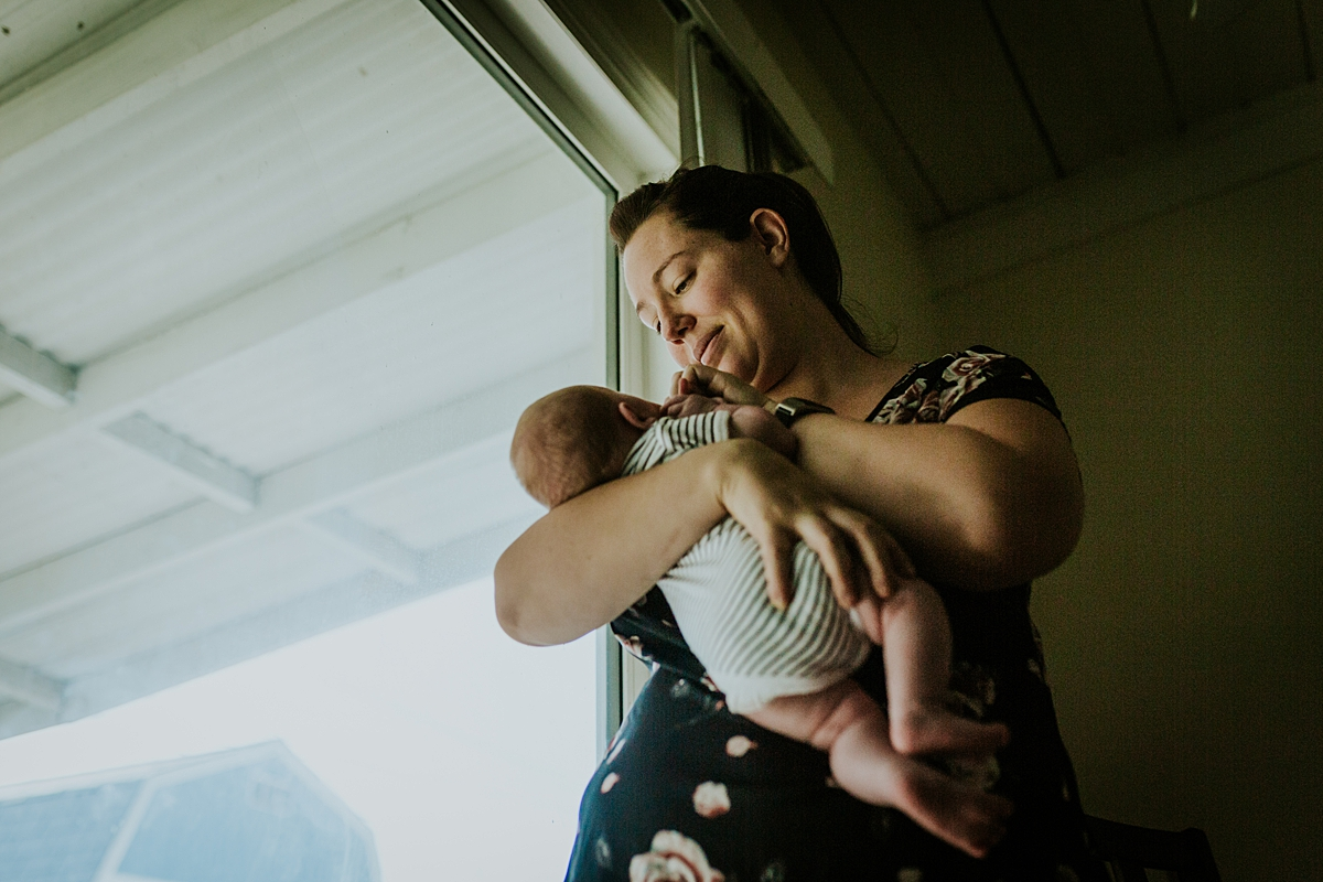 Orange County family photographer. Mom holds her newborn son while standing near the window during in home newborn session with Krystil McDowall Photography