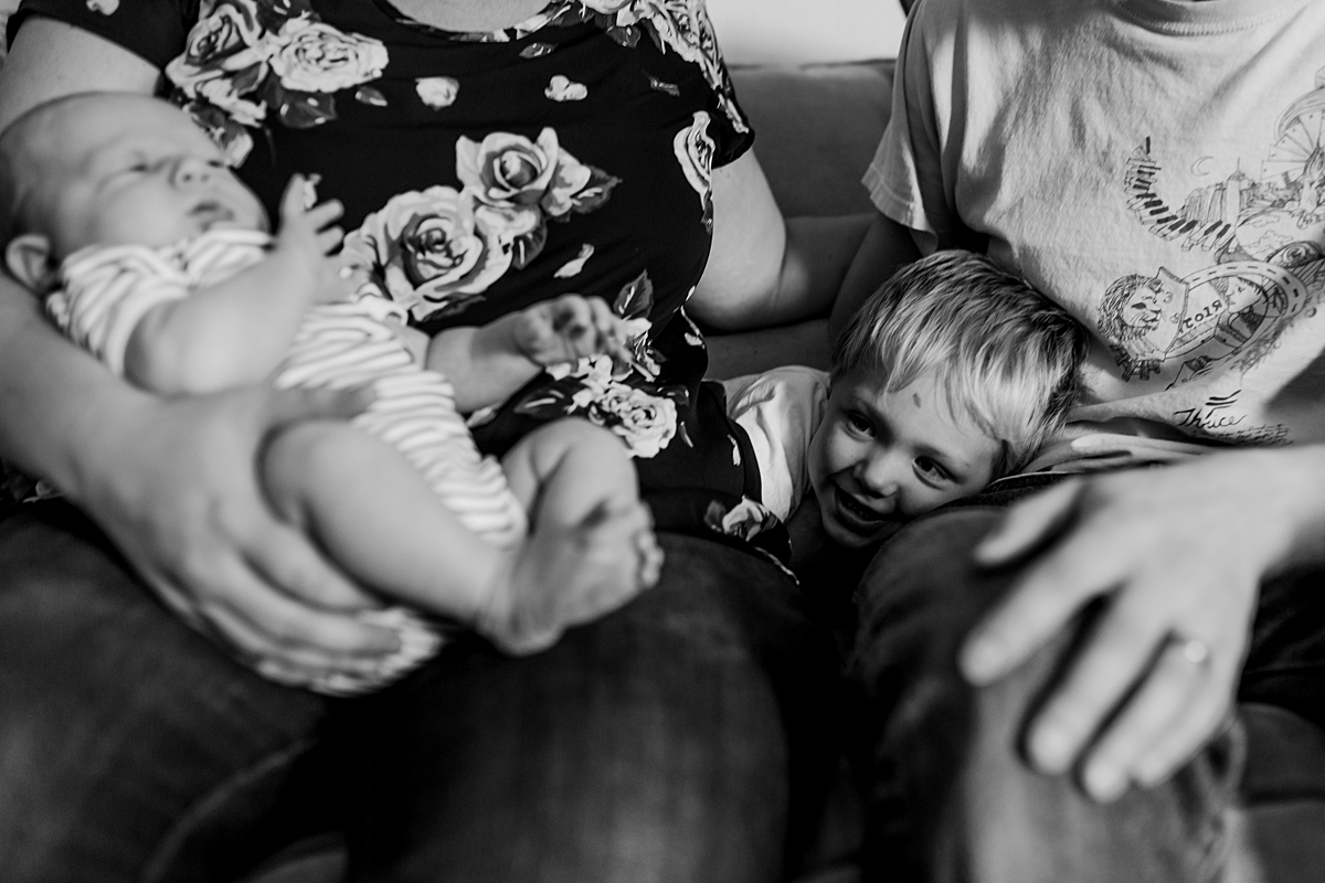 Orange County family photographer. Candid photo of older brother looking at his newborn brother while sitting on the couch during in home newborn session with Krystil McDowall Photography