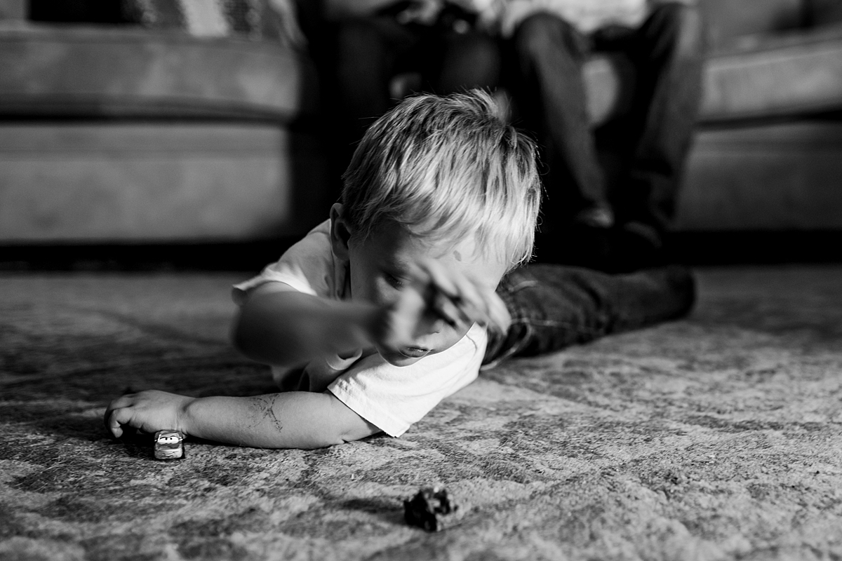 Orange County family photographer. Black and white candid photo of toddler playing with cars on the carpet while mom, dad and newborn son hang out in the background during in home newborn session