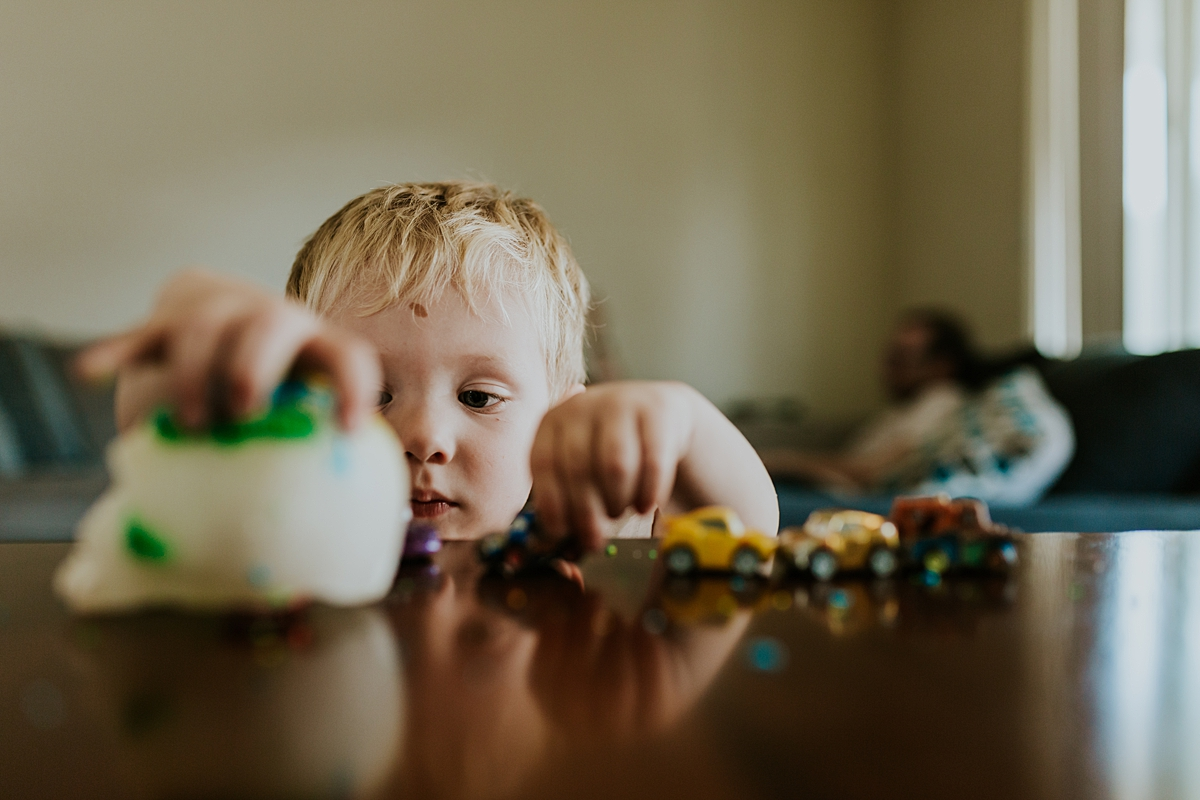 Orange County family photographer. Photo of young boy playing with cars in his living room during in home newborn session with Krystil McDowall Photography