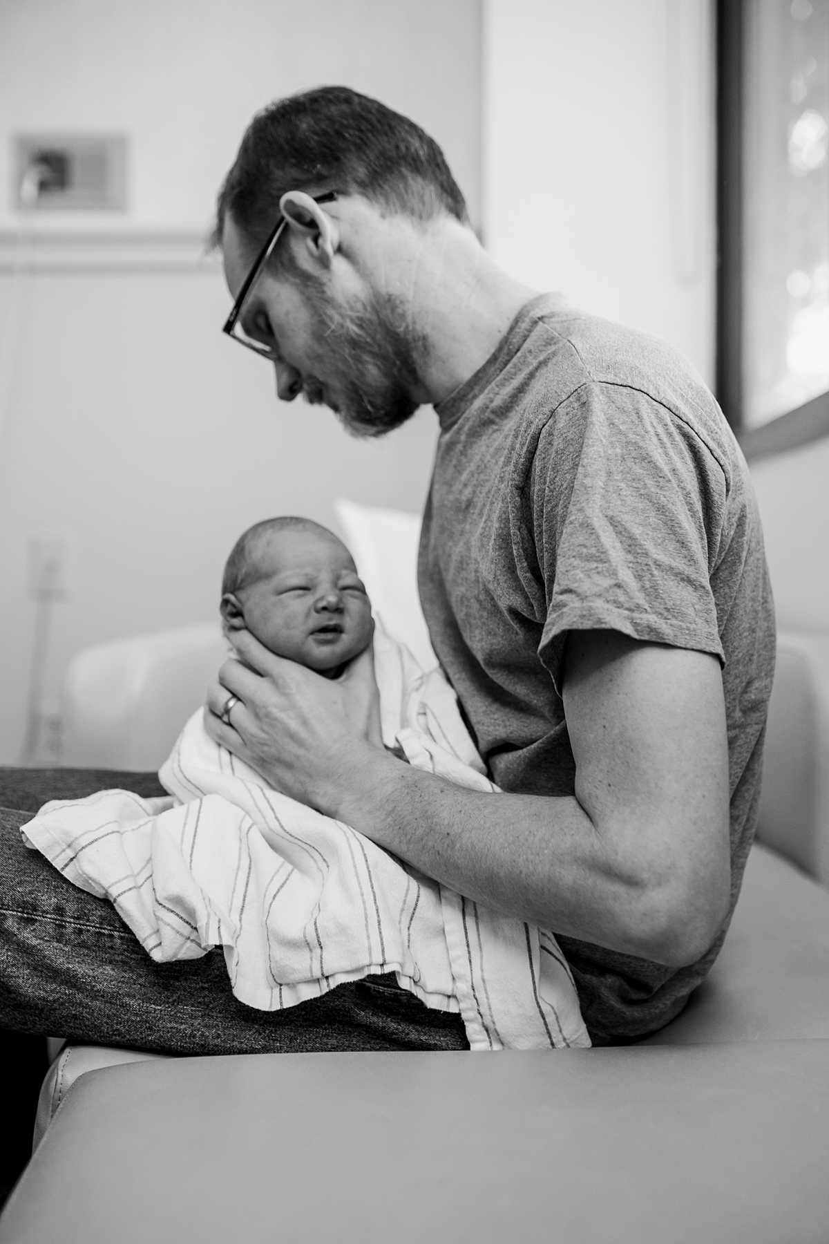 Orange County family photographer. Photo of dad gently holding his newborn son in the hospital at 2 day old during fresh 48 session with Krystil McDowall Photography