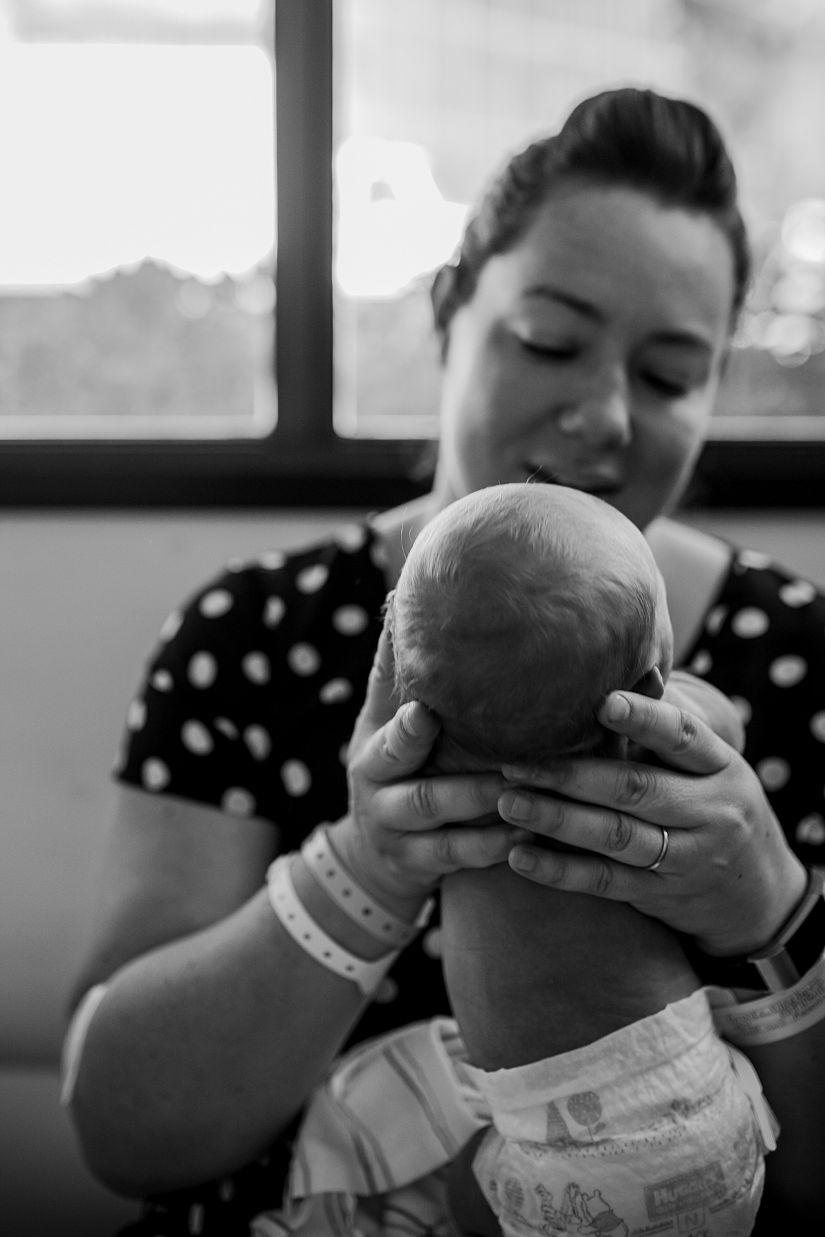 Orange County family photographer. Candid photo of mom holding her two day old newborn son in the hospital during fresh 48 session with Krystil McDowall Photography