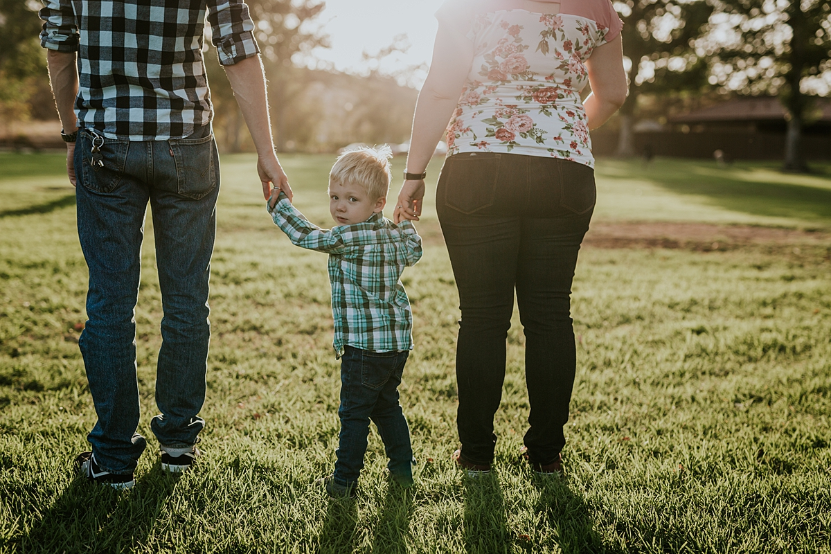 Orange County family photographer. Photo of pregnant mom with husband and blonde haired toddler standing in the grass at sunset during maternity photo shoot at Irvine Regional Park
