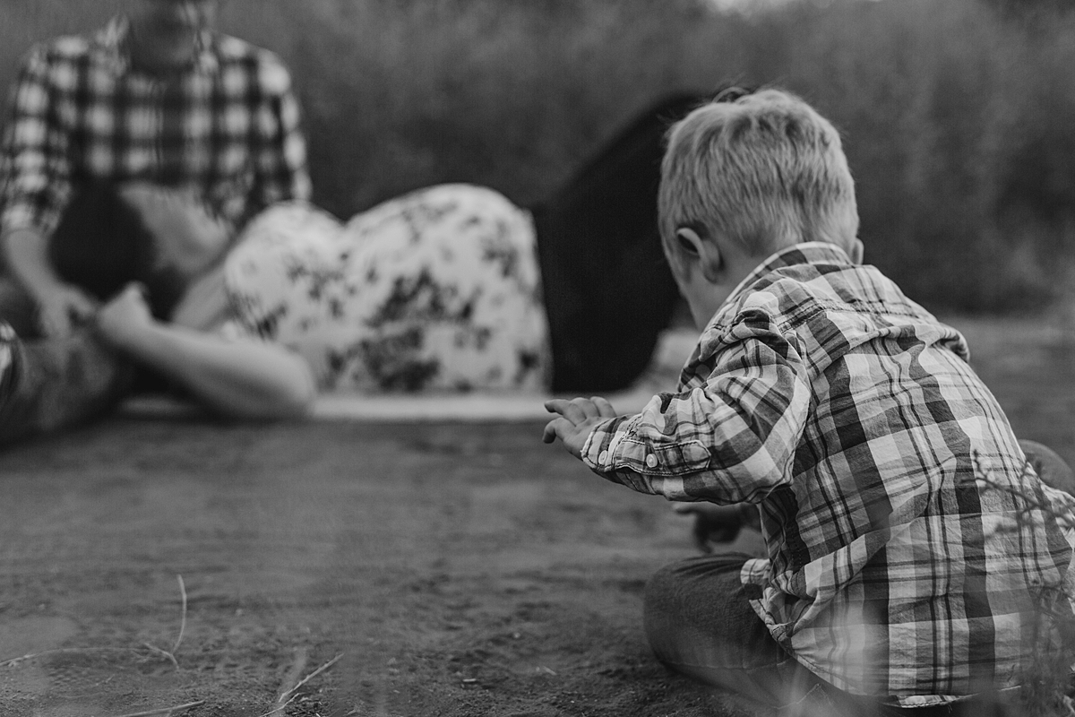 Orange County family photographer. Photo of young boy playing in the dirt with his mom and dad in the background during outdoor maternity photo session at Irvine Regional Park