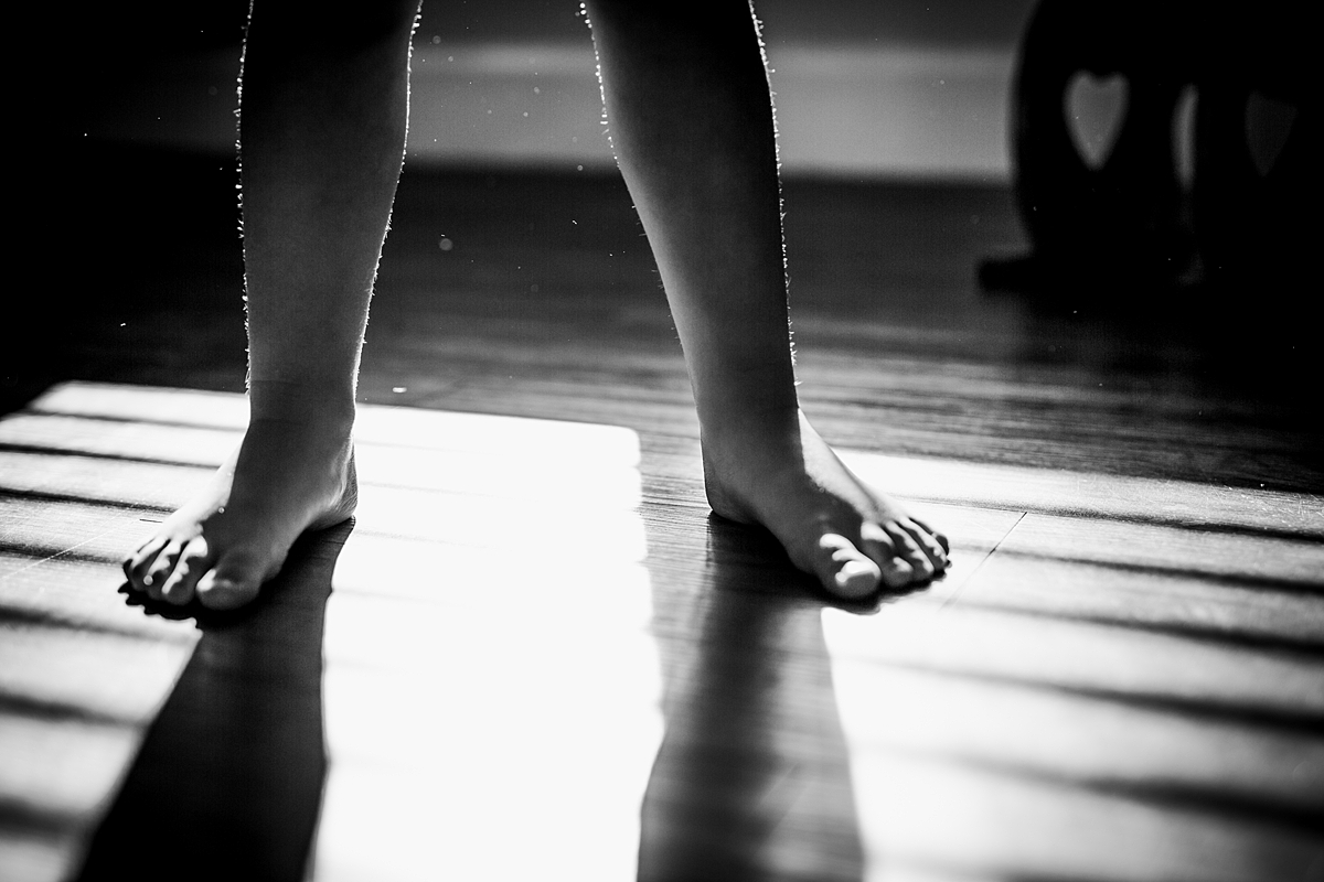 Orange County family photographer. Backlit photo of young girl's barefeet as she plays in the sun shining in her room taken during in home family session in Long Beach