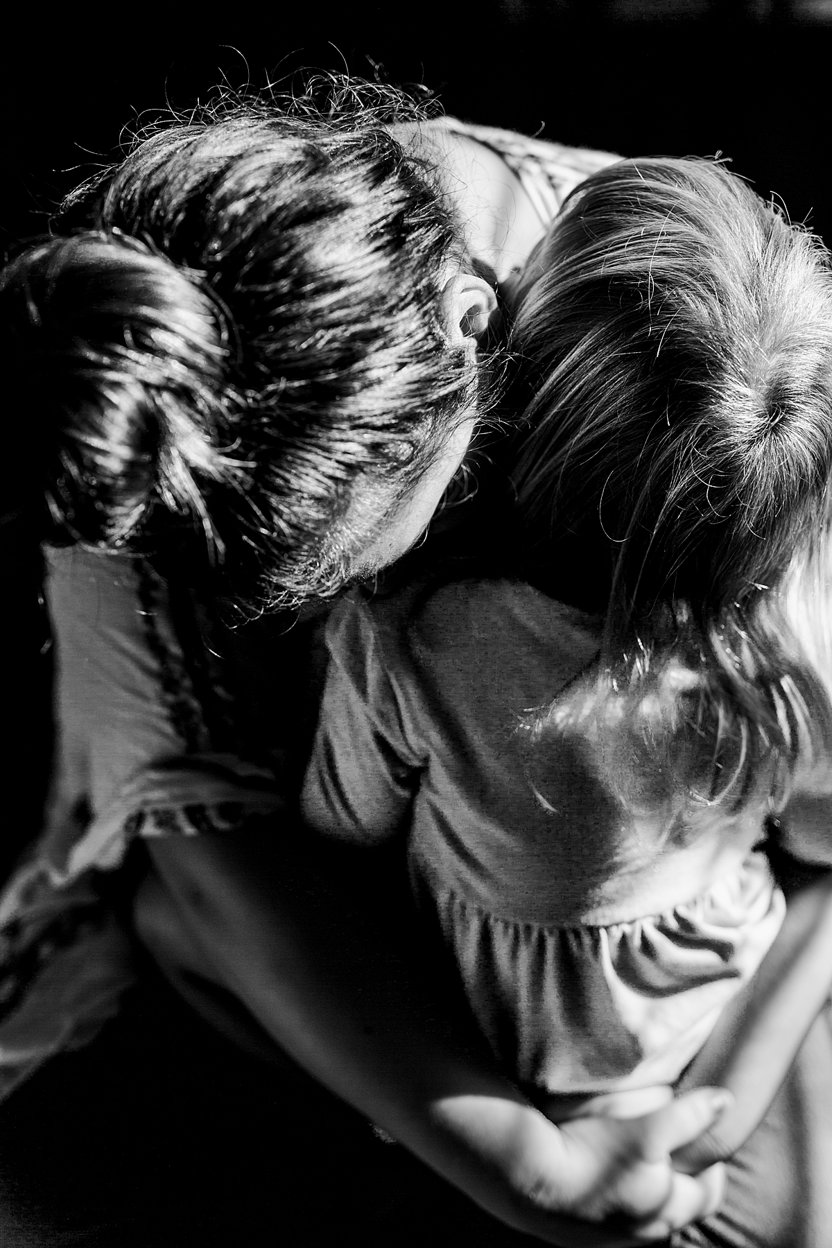 Orange County family photographer. Black and white photo of mom embracing her daughter while sitting on the floor during in home family photo session in Long Beach, CA