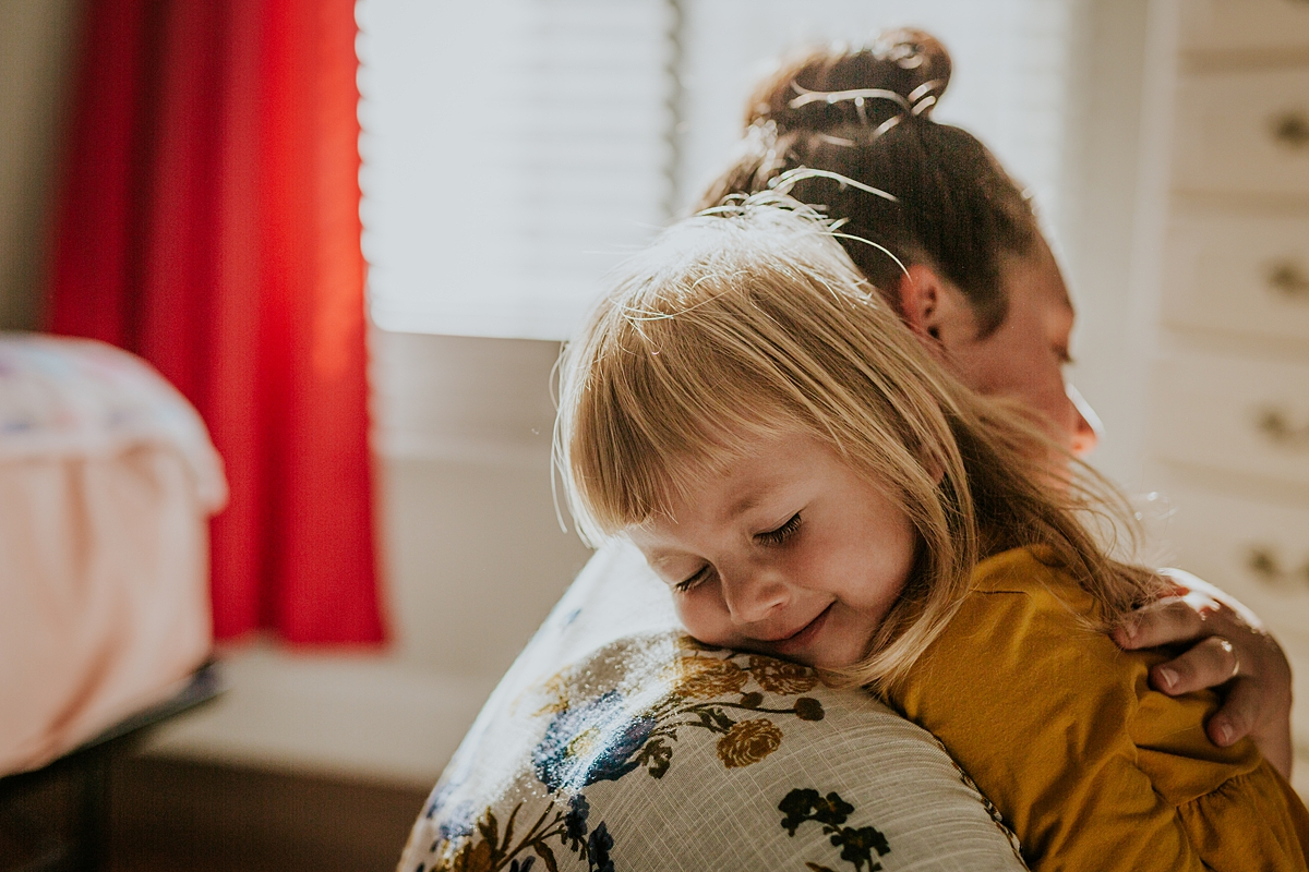 Orange County family photographer. Candid photo of mom embracing her daughter while sitting on the floor during in home family photo session in Long Beach, CA