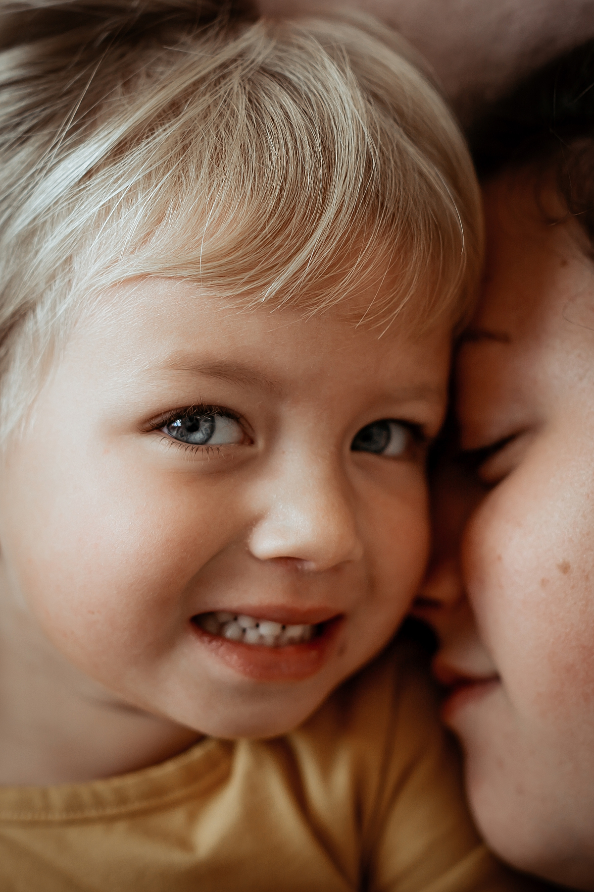 Orange County family photographer. Close up photo of mom and daughter's heads touching as they lay on daughter's bed during in home family photo session in Long Beach, CA