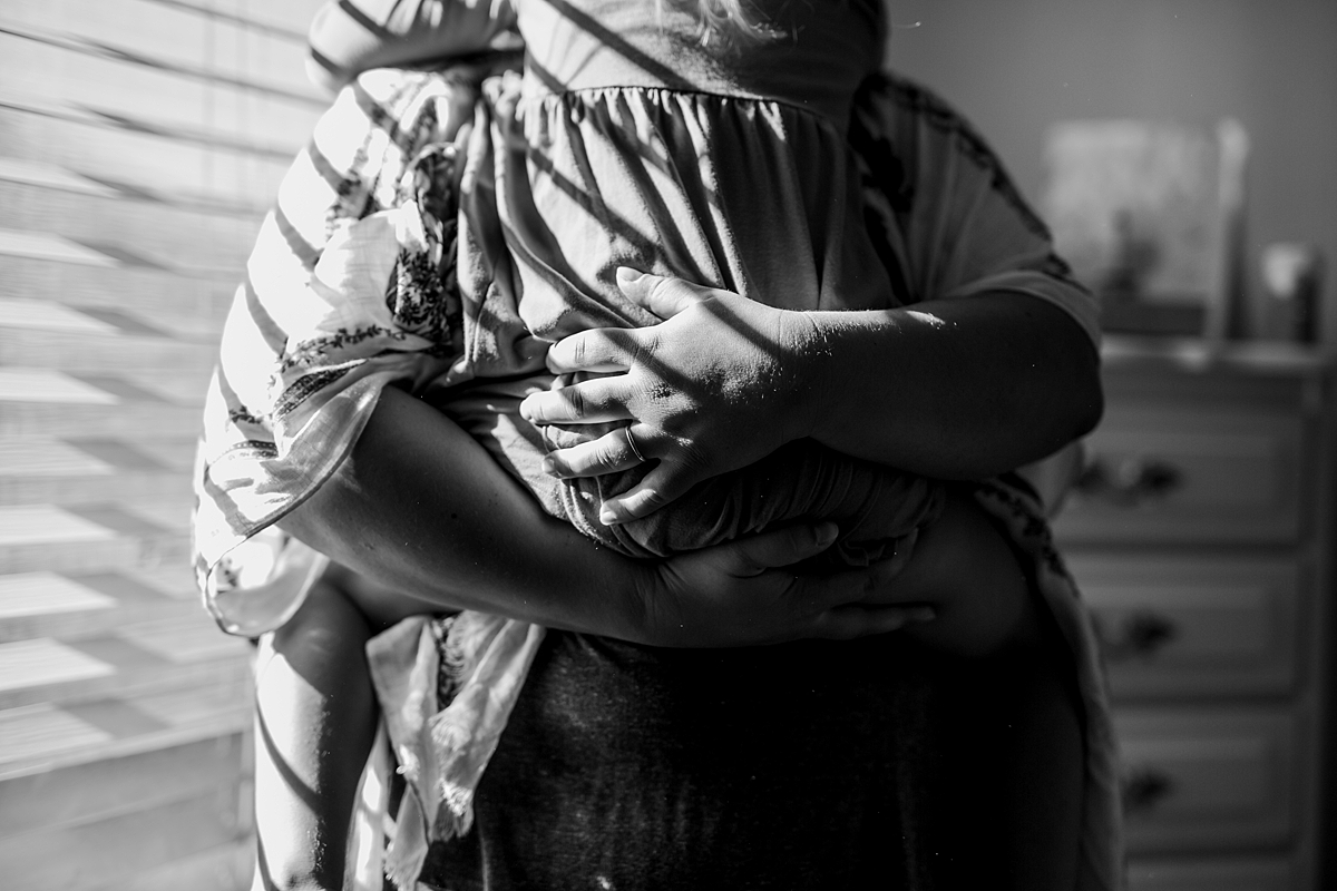 Orange County family photographer. Details photo of mom holding her daughter while standing against sun drenched window in daughter's bedroom during in home family photo session in Long Beach, CA
