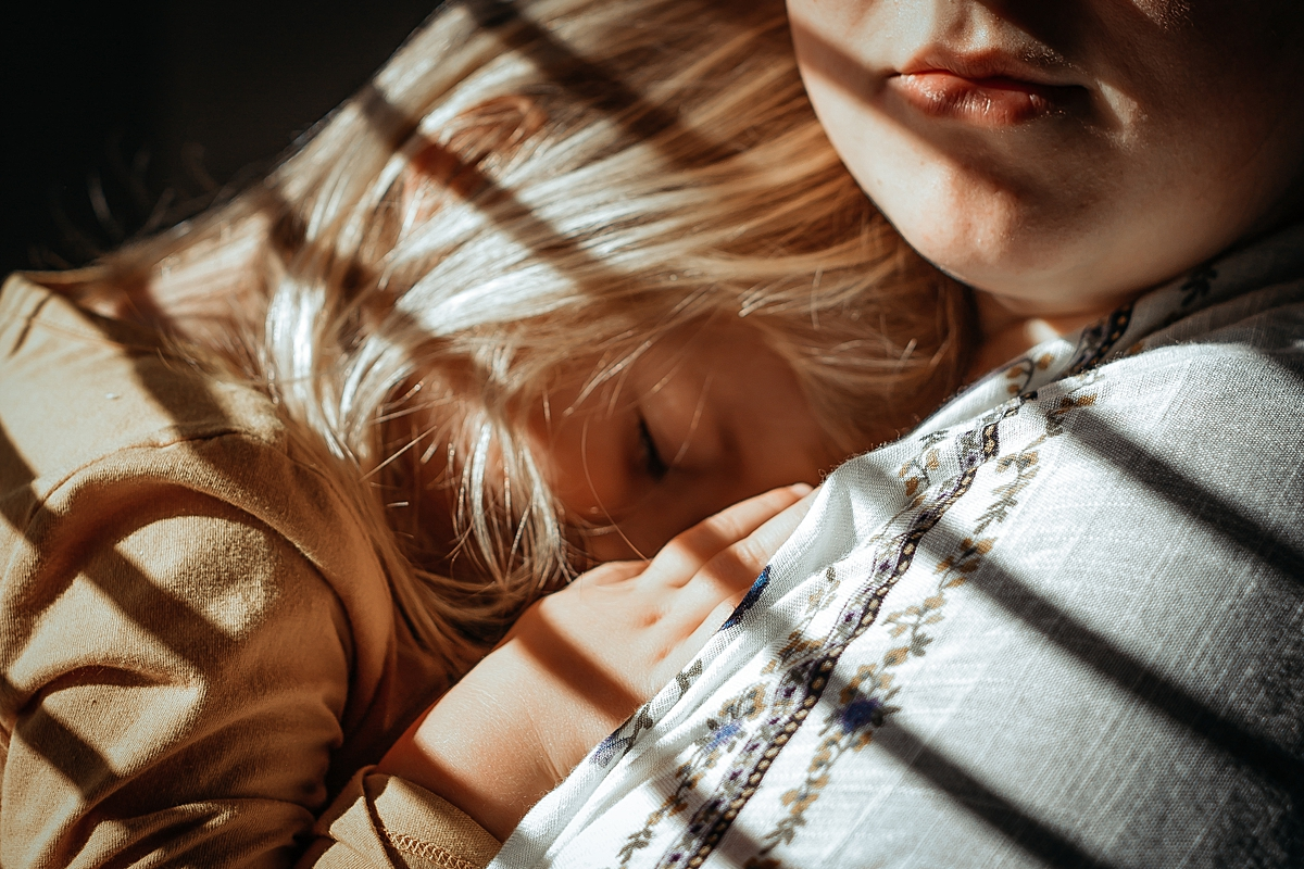Orange County family photographer. Close up photo of daughter cuddling into mom's chest while standing in sun drenched window in daughter's bedroom during in home family photo session in Long Beach