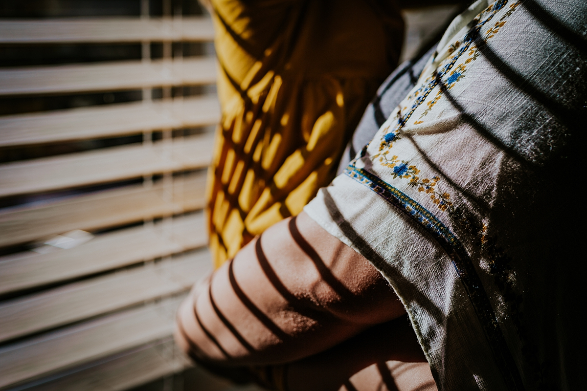 Orange County family photographer. Details photo of mom's arms wrapped around her daughter while standing in sun drenched window in daughter's bedroom during in home family photo session in Long Beach