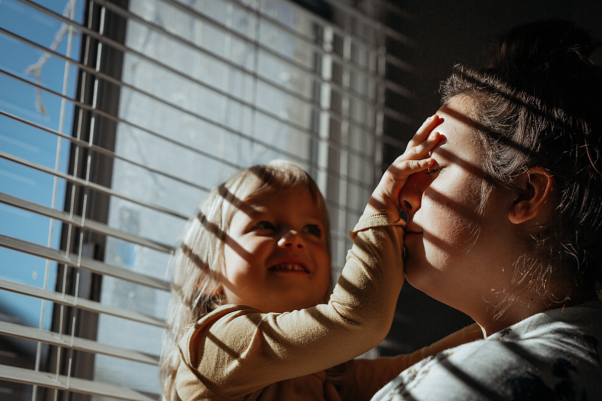 Orange County family photographer. Photo of daughter being silly and covering mom's face as they sit in sun drenched window in daughter's bedroom during in home family photo session in Long Beach, CA
