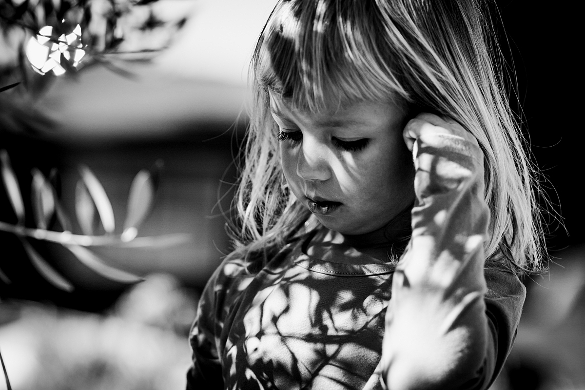 Orange County family photographer. Photo of girl in her front yard in the shadows of the bush out front during in home family photo session in Long Beach, CA
