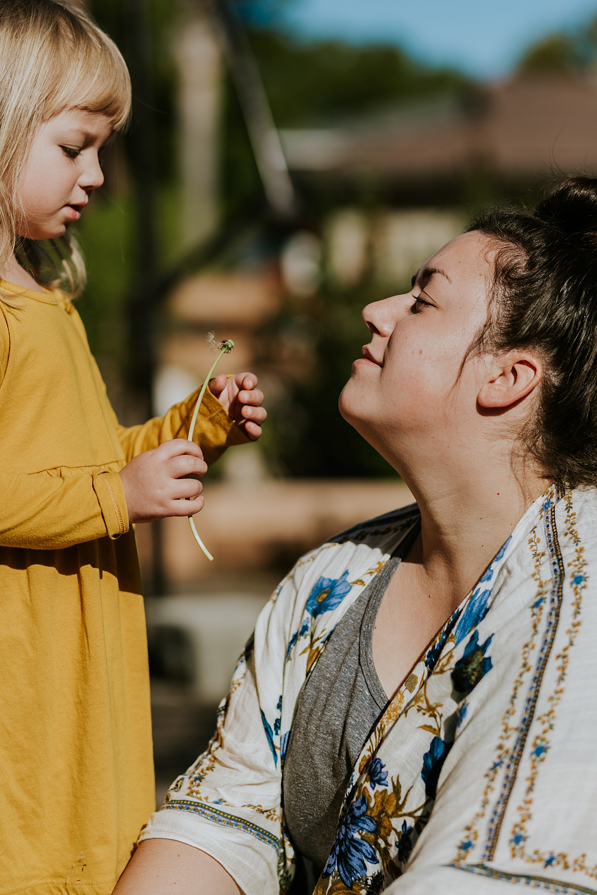 Orange County family photographer. Photo of mom and daughter discussing the flowers while sitting in their front yard during in home family photo session in Long Beach, CA
