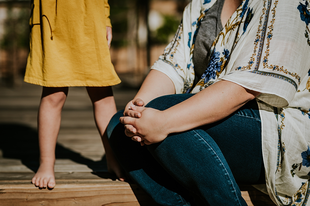 Orange County family photographer. Details photo of mom and daughter's legs as they sit in their front yard during in home family photo session in Long Beach, CA
