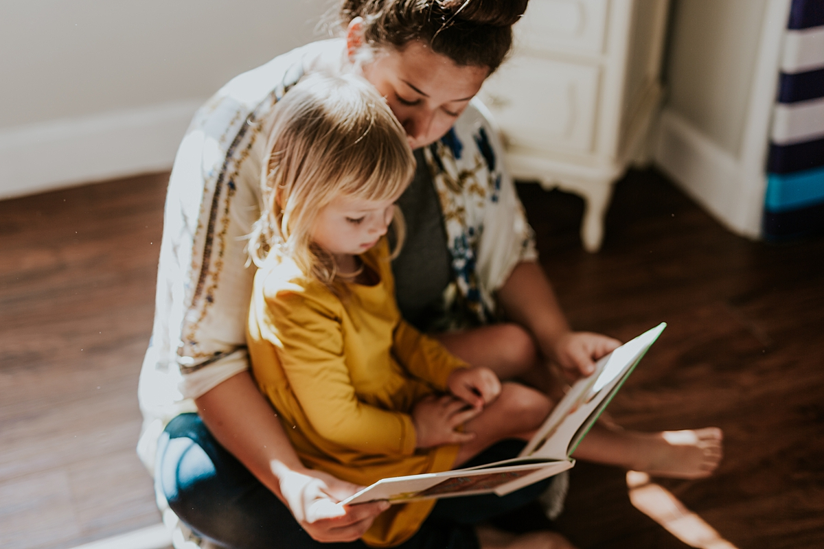 Orange County family photographer. Photo of mom and daughter reading a book together during in home family photo session in Long Beach, CA
