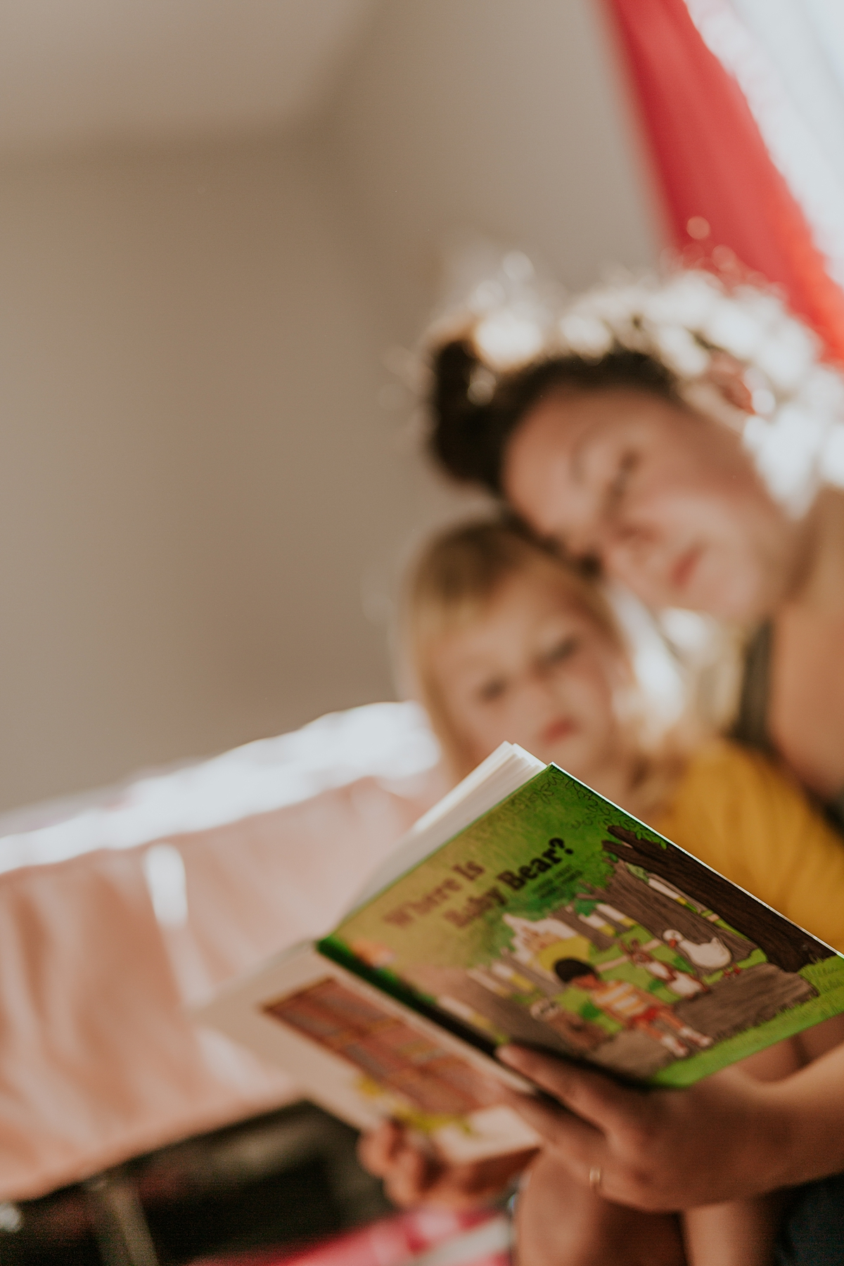 Orange County family photographer. Photo of mom and daughter reading a bear book in daughter's bedroom during in home family photo session in Long Beach, CA