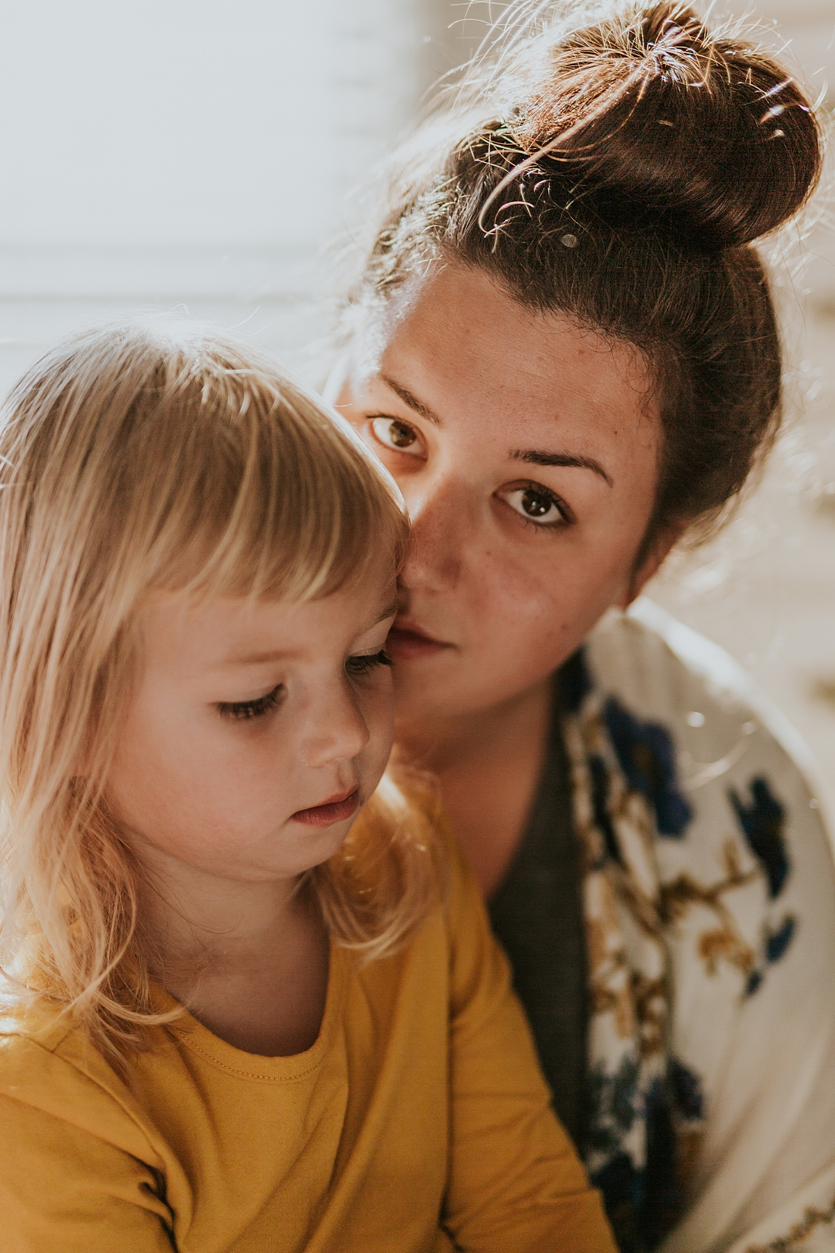 Orange County family photographer. Photo of mom and her daughter reading during in home family photo session in Long Beach, CA