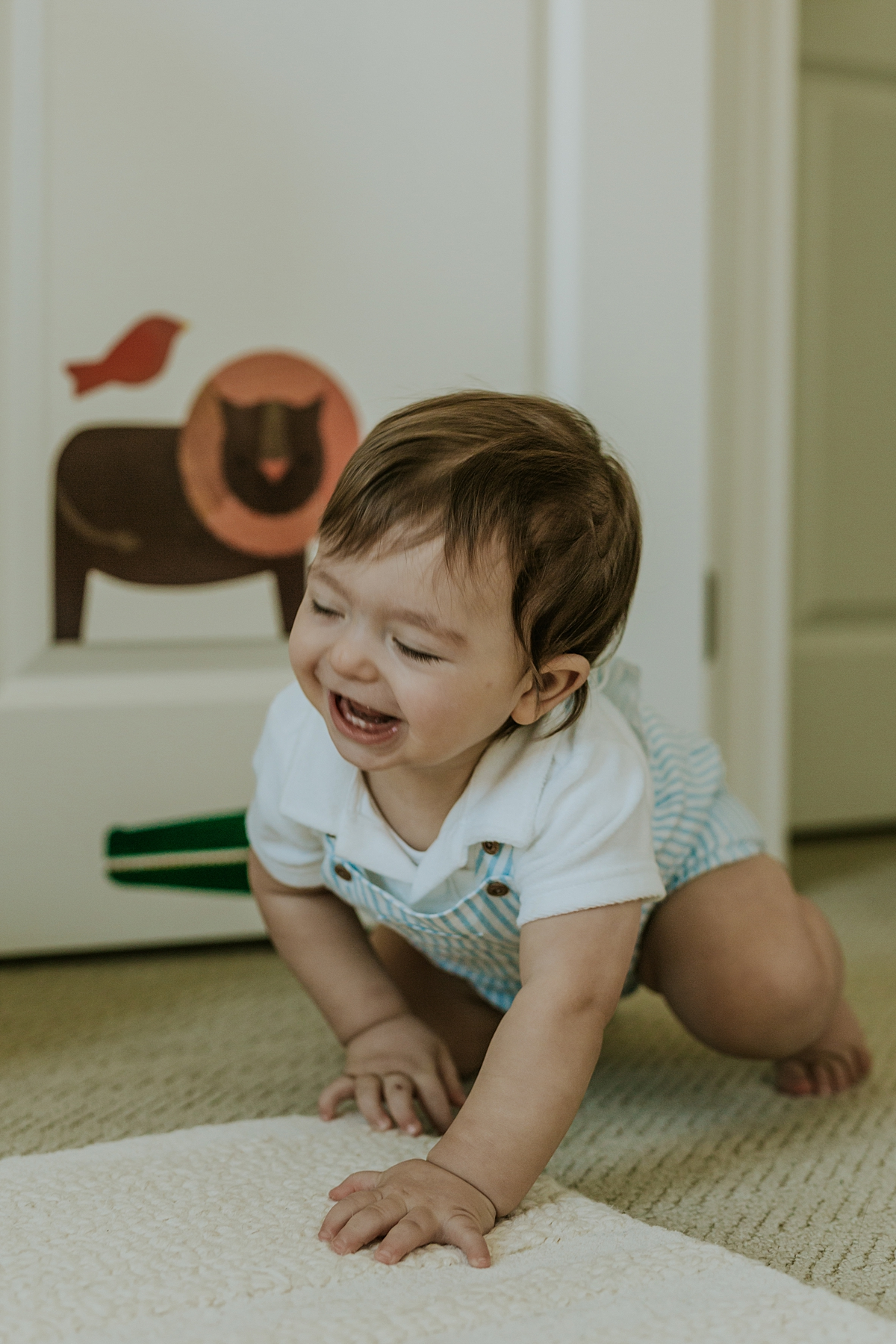 Orange County family photographer. Photo of one year old in blue striped overalls crawling during in home session in Irvine CA