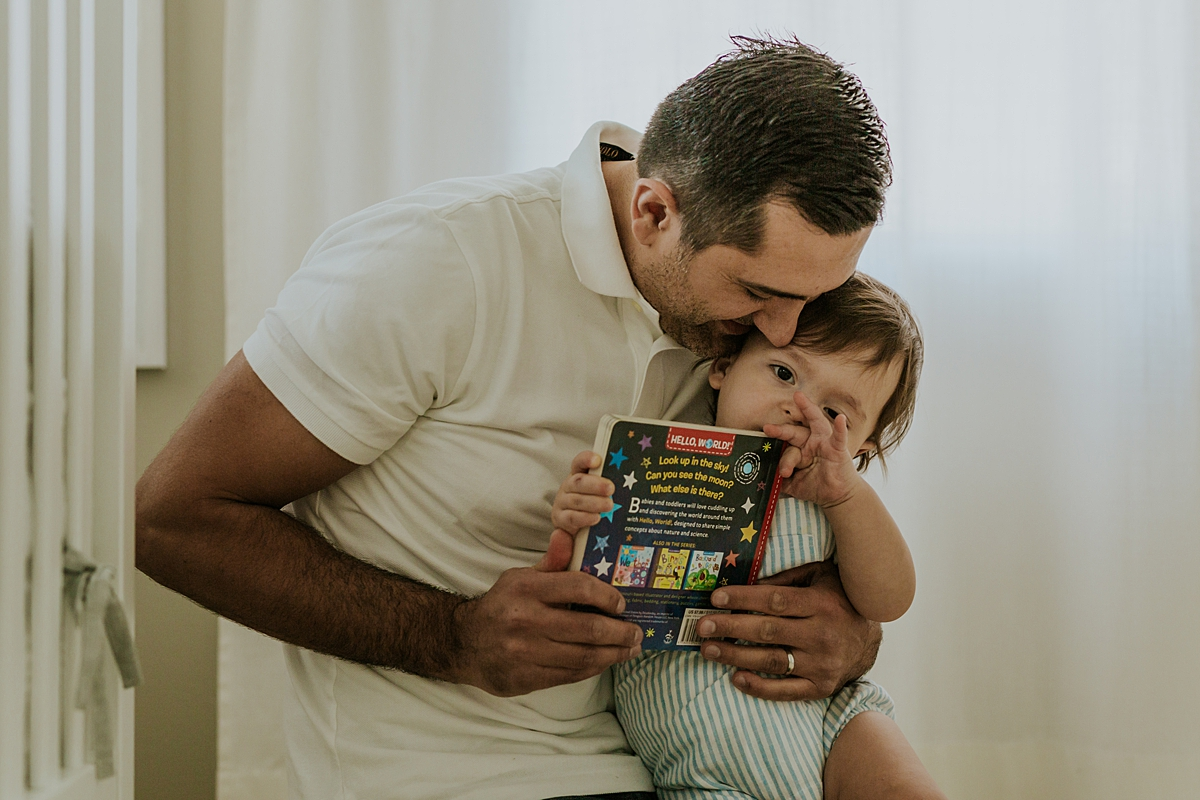 Orange County family photographer. Photo of dad and son cuddling while reading stories during in family photo session in Irvine CA