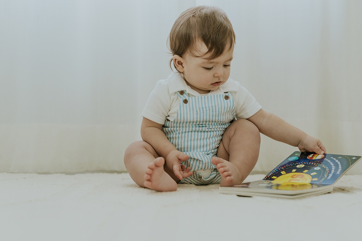 Orange County family photographer. Photo of one year old boy reading his book in his room during in family photo session in Irvine CA
