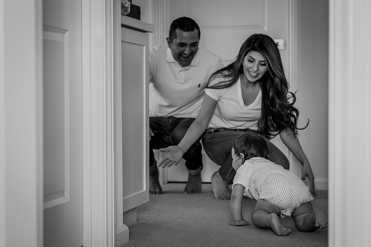 Orange County family photographer. Photo of one year old boy crawling from his room to his parents during family photo session in Irvine CA