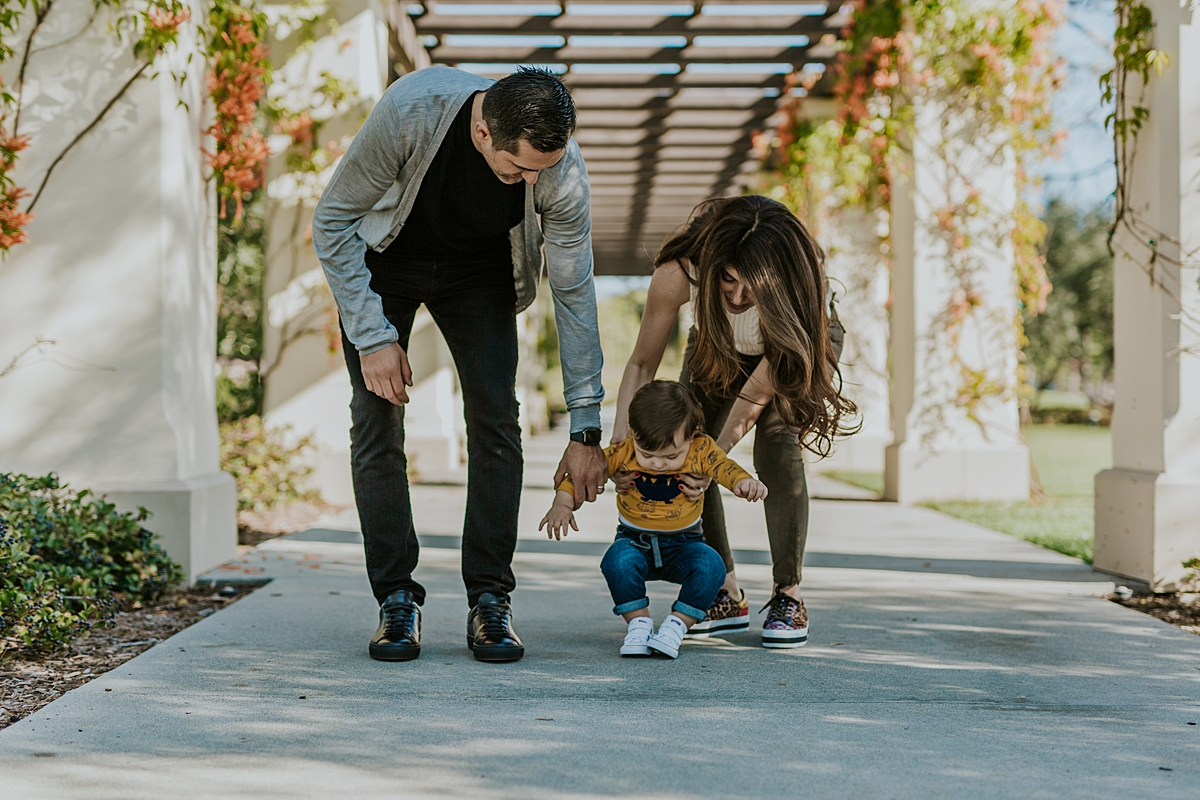 Orange County family photographer. Candid photo of mom, dad and one year old boy walking at local Irvine park during family photo session in Irvine CA