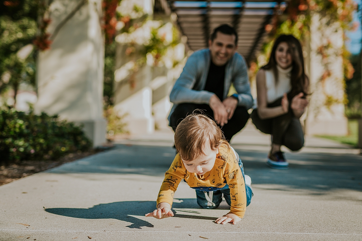 Orange County family photographer. Candid photo of boy crawling footpath with parents in the background during family photo session in Irvine CA