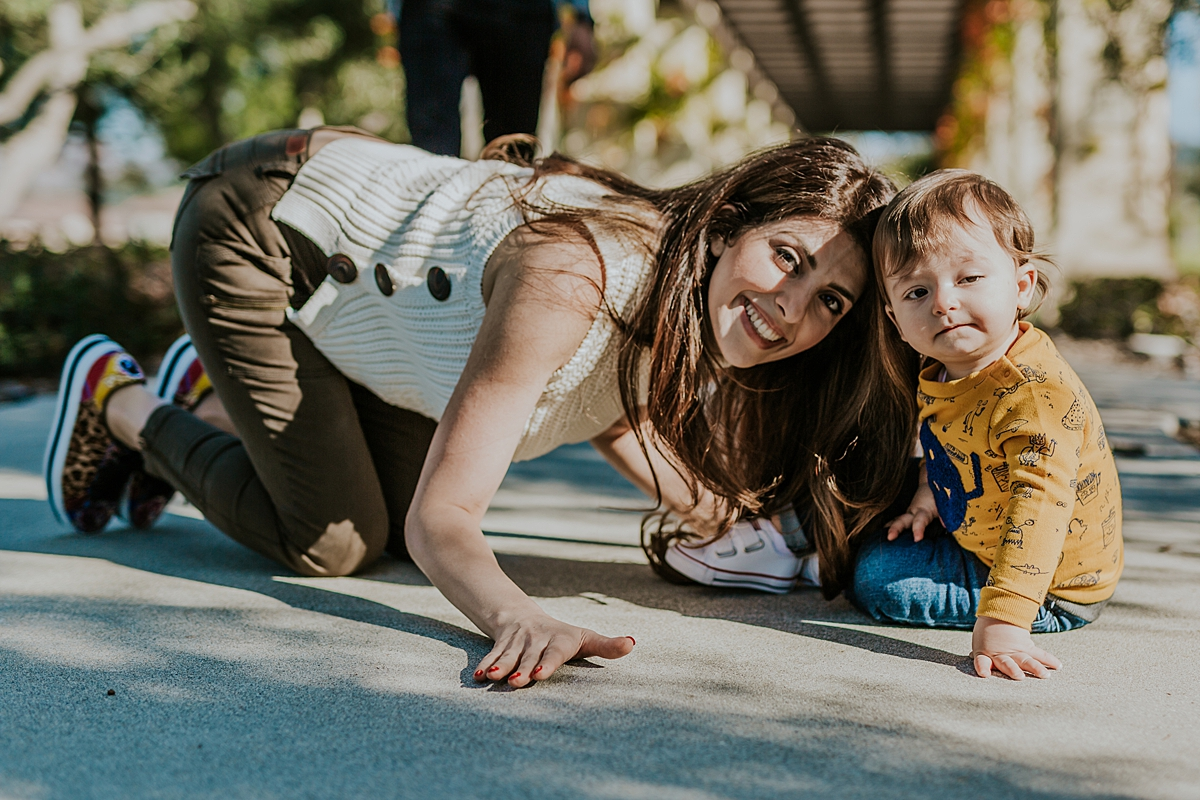 Orange County family photographer. photo of mom and son sitting together on park foopath at local Irvine park during family photo session in Irvine CA