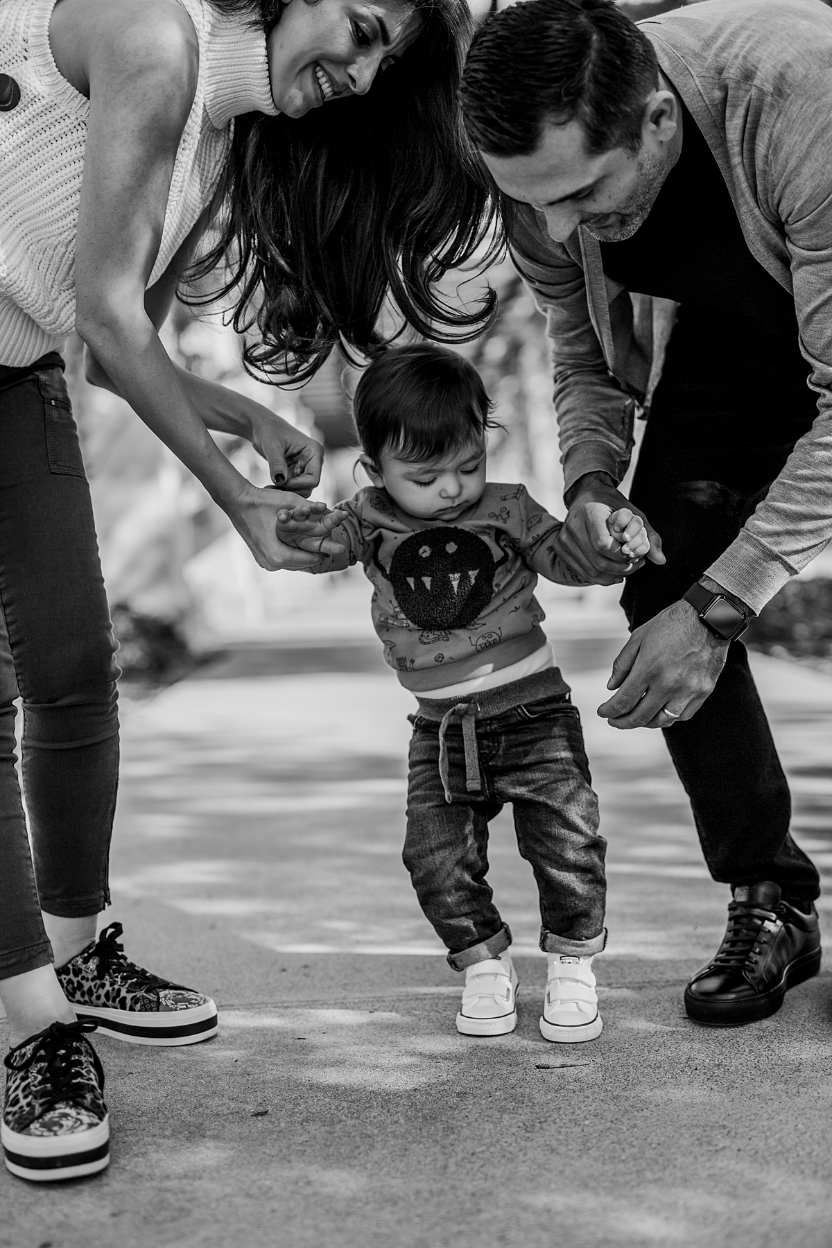 Orange County family photographer. photo of mom, dad and son walking together at local Irvine park during family photo session in Irvine CA