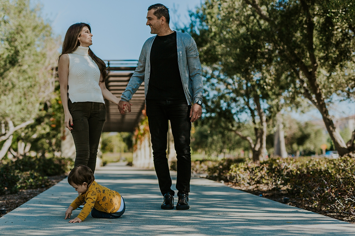 Orange County family photographer. photo of mom and dad holding hands with their sweet son playing on the footpath in front during family photo session in Irvine CA