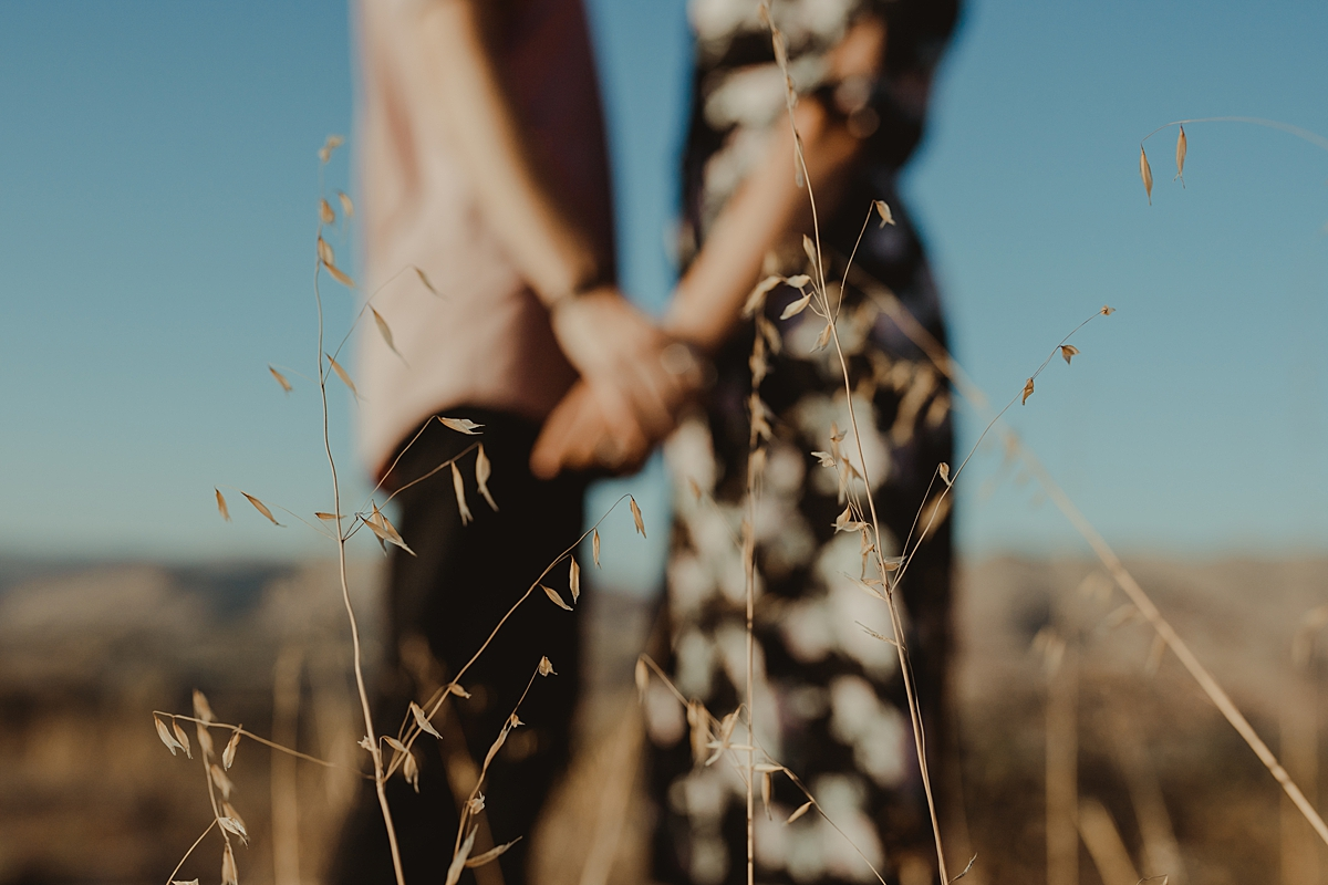 Orange County family photographer. Photo of married couples hands as they stand amongst the grass in outdoor couples photo session at Irvine Regional Park