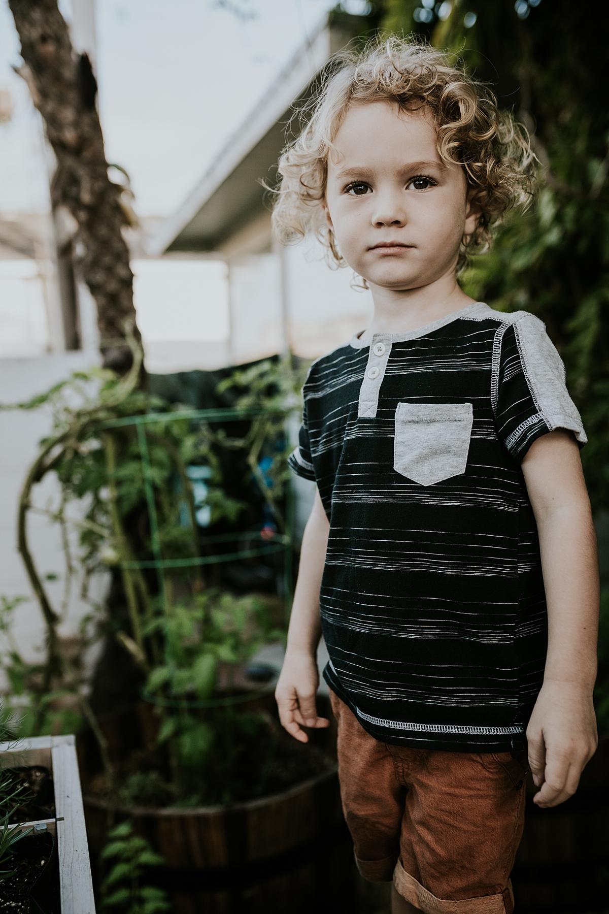 Orange County family photographer. Cute curly blonde haired boy stands in his front yard during in home session at Huntington Beach