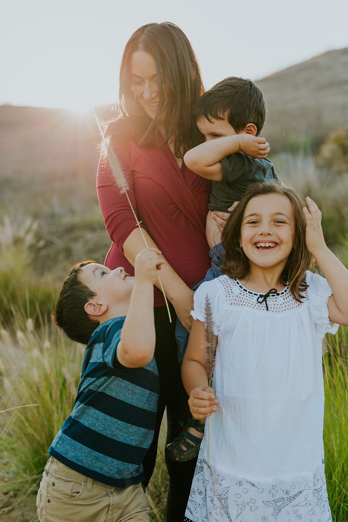 Orange County family photographer. Photo of mom and her three young kids among the long green grass at Irvine Regional Park