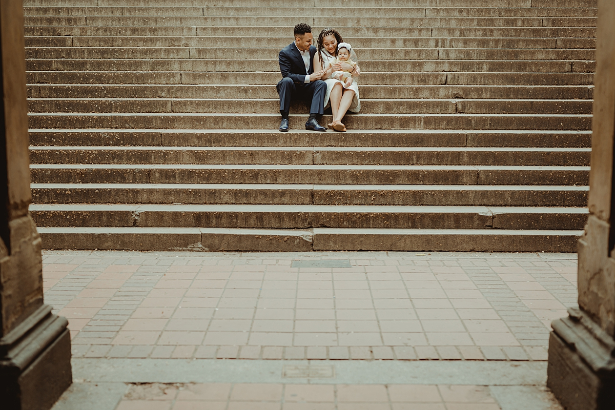 Orange County family photographer. Photo of family of three sitting on large set of stairs during outdoor family photo session with Krystil McDowall Photography